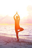Woman doing yoga on sunset beach Stock Images