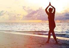 Woman doing yoga on sunset beach Stock Image
