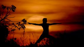 Woman doing yoga at the sunset stock footage