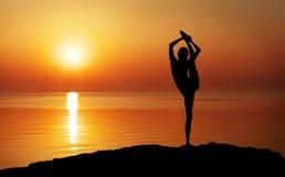 Woman doing Yoga at sunset Royalty Free Stock Photos