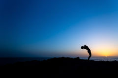 Woman doing yoga sunset silhouette Stock Photos