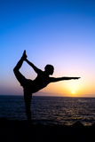 Woman doing yoga sunset silhouette. Young woman doing yoga pose king dancer, sunset silhouette in mountains and sea ocean. Sport and exercising in beautiful Royalty Free Stock Photography