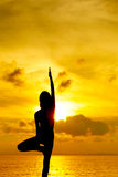 Woman doing yoga at sunset time Stock Image