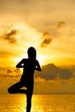 Woman doing yoga at sunset time Stock Photos