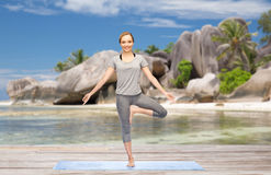 Woman doing yoga in tree pose on beach Royalty Free Stock Photography