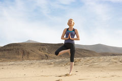 Woman Doing Yoga Tree Pose, Desert and Hills in Background Stock Photo