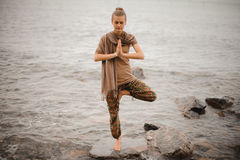 Woman doing yoga tree pose namaste on the stone near the ocean Stock Images