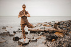 Woman doing yoga tree pose namaste on the stone near the ocean Royalty Free Stock Image