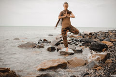 Woman doing yoga tree pose namaste on the stone near the ocean Stock Photography