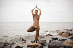 Woman doing yoga tree pose on the stone near the ocean Royalty Free Stock Photo