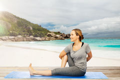 Woman doing yoga in twist pose on beach. Fitness, people and healthy lifestyle concept - woman doing yoga in twist pose on mat over exotic tropical beach Stock Photo