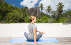 Woman doing yoga in twist pose on beach. Fitness, people and healthy lifestyle concept - woman doing yoga in twist pose on mat over exotic tropical beach Royalty Free Stock Image