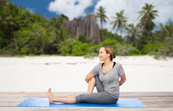 Woman doing yoga in twist pose on beach. Fitness, people and healthy lifestyle concept - woman doing yoga in twist pose on mat over exotic tropical beach Royalty Free Stock Photography