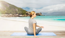 Woman doing yoga in twist pose on beach. Fitness, people and healthy lifestyle concept - woman doing yoga in twist pose on mat over exotic tropical beach Stock Photos