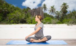 Woman doing yoga in twist pose on beach. Fitness, sport and healthy lifestyle concept - woman doing yoga in twist pose on mat over exotic tropical beach Royalty Free Stock Photography