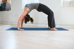 Woman doing yoga - Urdhva Dhanurasana pose Stock Photos