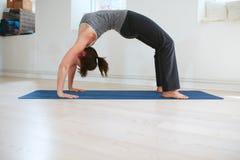 Woman doing yoga - Urdhva Dhanurasana pose Stock Photos