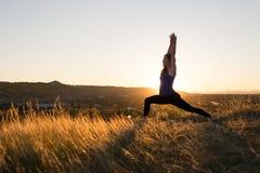 Woman doing yoga warrior I pose during sunset Royalty Free Stock Photos