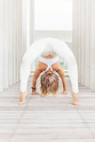 Woman doing yoga in a white room Royalty Free Stock Photos