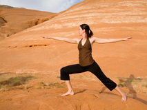 Woman Doing Yoga in Wilderness. Woman doing yoga in the wilderness at sunset against a beautiful wilderness backdrop at Lake Powell, Glen Canyon National Royalty Free Stock Images