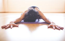 Woman doing yoga at wooden floor Royalty Free Stock Image