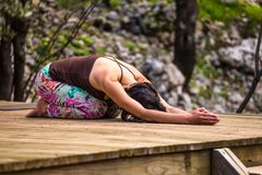 Woman doing yoga in the yard. A slender brunette lies on the wooden floor of an old house. The girl is doing asana. Beautiful female back stock photos