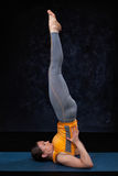 Woman doingh Ashtanga Vinyasa Yoga inverted asana Salamba sarvan. Gasana - supported shoulderstand on dark grunge background Stock Photos