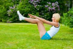 Woman doinng pilates exercises. Beautiful caucasian woman doing pilates exercises in the park Stock Photos