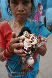 Woman with a doll of Krishna in hands Stock Photo