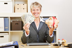 Woman with dollar bills and piggy. Smiling happy elderly business woman with dollar bills and a piggy bank Royalty Free Stock Photo