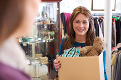 Woman Donating Unwanted Items To Charity Shop Stock Images