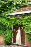The woman at the door. Romantic woman standing near old doors under a bush of blossoming bougainvillea Stock Photos