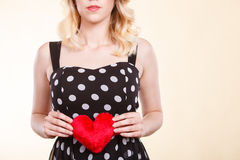 Woman in dotted dress holding red heart Stock Images