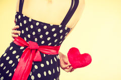 Woman in dotted dress holding red heart Stock Image
