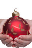 Woman Double Hand Holding a Bauble. A red and gold christmas bauble being held with both hands by a woman on a white background Stock Photography