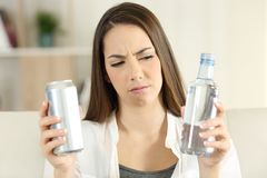 Woman doubting between soda drink and water Royalty Free Stock Photo
