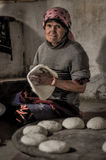 Woman with dough in Tajikistan. Wakhan valley, Tajikistan - circa October 2011: Older woman with pink headcloth sits on ground and kneads dough in Wakhan valley Royalty Free Stock Photography