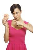 Woman with doughnut. Young woman holding a doughnut looking guilty Stock Photos