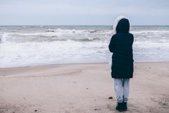 Woman in down jacket looking at ocean. On grey windy day. Rear view, full height Stock Image