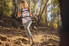 Woman on downhill run over rocky trail. Female runner in extreme mountain race competition royalty free stock photo