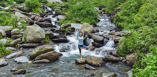 Woman dpoing yoga asana tree pose at waterfall Royalty Free Stock Photo
