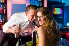 Woman dragging barkeeper in club or bar Stock Photo