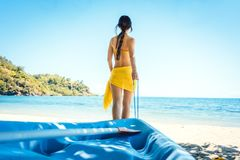 Woman dragging her boat to the water on the beach. For watersports royalty free stock photos