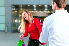 Woman dragging man into shopping mall Royalty Free Stock Photo
