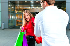 Woman dragging man into shopping mall Royalty Free Stock Photography