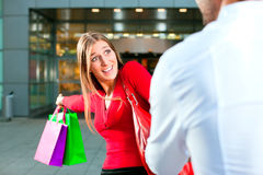 Woman dragging man into shopping mall Stock Photography