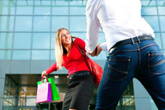 Woman dragging man into shopping mall Stock Photos