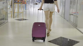 Woman is dragging a suitcase stock video footage