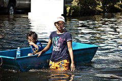 Woman drags a boat that carries her child. BANGKOK - NOVEMBER 13: An unidentified woman drags a boat which carries her daughter in the flooded area at Bang Khen Royalty Free Stock Photo