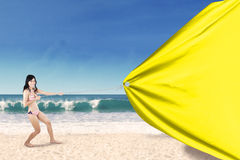 Woman drags empty banner at coast Royalty Free Stock Photos